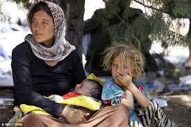 Ba mẹ con Yazidi ngồi nghỉ mệt